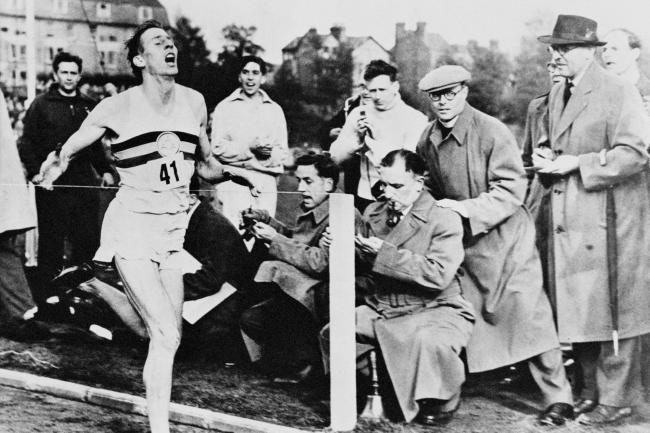 Sir Roger Bannister crosses the finish line to become the first man to run a sub-four minute mile at Iffley Road, Oxford
