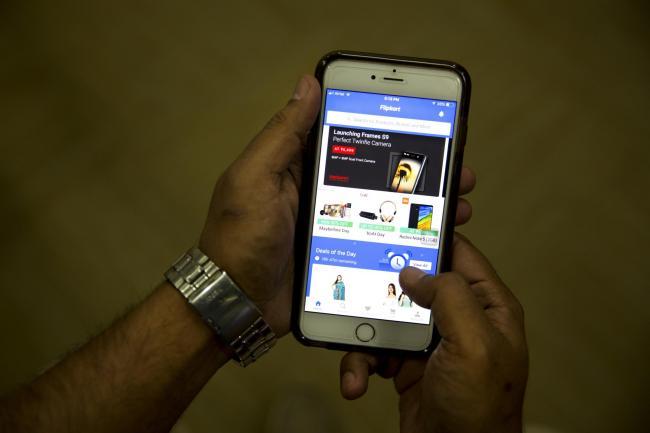 An Indian man checks the Flipkart site on his mobile phone in New Delhi (AP
