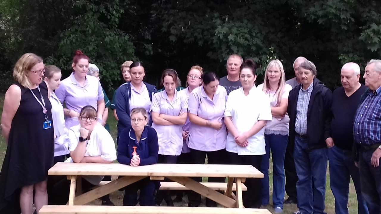 Staff at Edgeley House Nursing Home with the bench presented by the family of Graham Welch