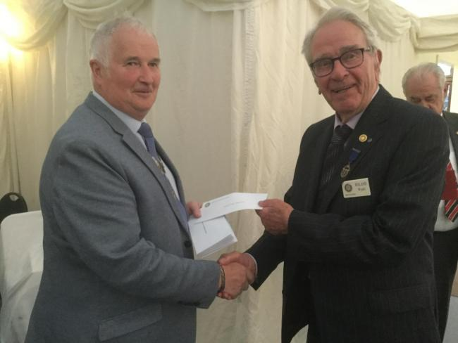 Wem Rotary chairman Peter Broomhall presents Roly Wyatt from Whitchurch Rotary with a cheque
